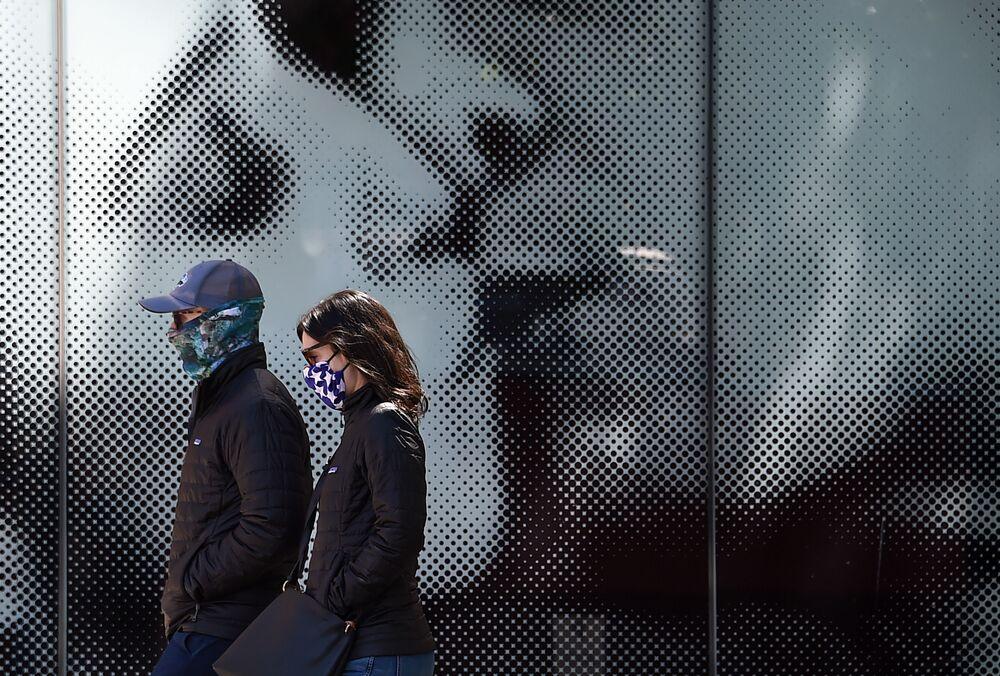Casal com máscaras passa em frente a cartaz de filme em cinema de Washington, EUA