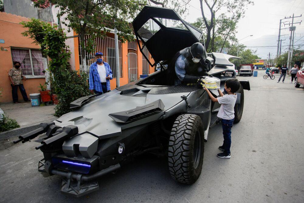 Advogado Candelario Maldonado, vestido como o Batman e usando máscara, dá bolo para criança durante seu aniversário em Monterrey, México