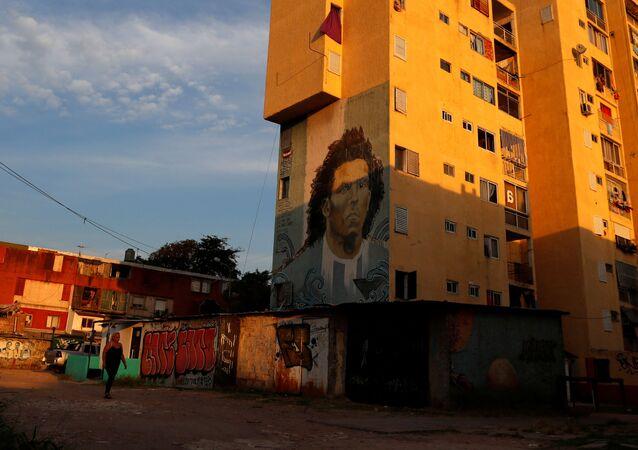 Mulher caminha em frente a grafite de Carlos Tevez nos arredores de Buenos Aires durante pandemia do coronavírus