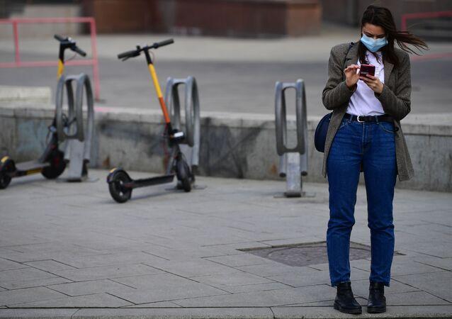 Garota com celular e máscara protetora na rua Bolshaya Dmitrovka em Moscou durante o regime de confinamento dos cidadãos