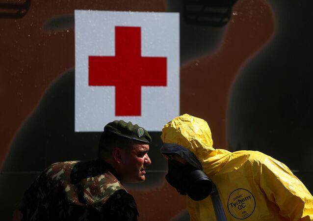 Um oficial do Exército brasileiro e um membro do Batalhão de Defesa Química, Biológica, Radiológica e Nuclear, conversam durante uma demonstração de táticas de combate à pandemia do novo coronavírus. A ação foi realizada no quartel general do Exército no Rio de Janeiro no dia 14 de abril de 2020.