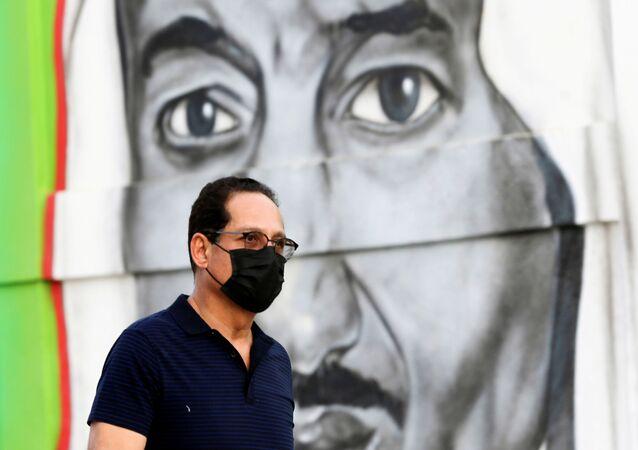 Um homem saudita caminha de máscara em frente a uma imagem do rei Salma bin Abdulaziz, em Riade, no dia 25 de março de 2020.