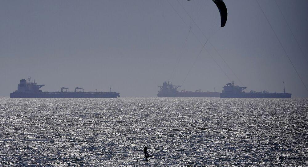 Um kitesurfista pegando ondas em meio a petroleiros ancorados, 22 de abril, Huntington Beach, Califórnia