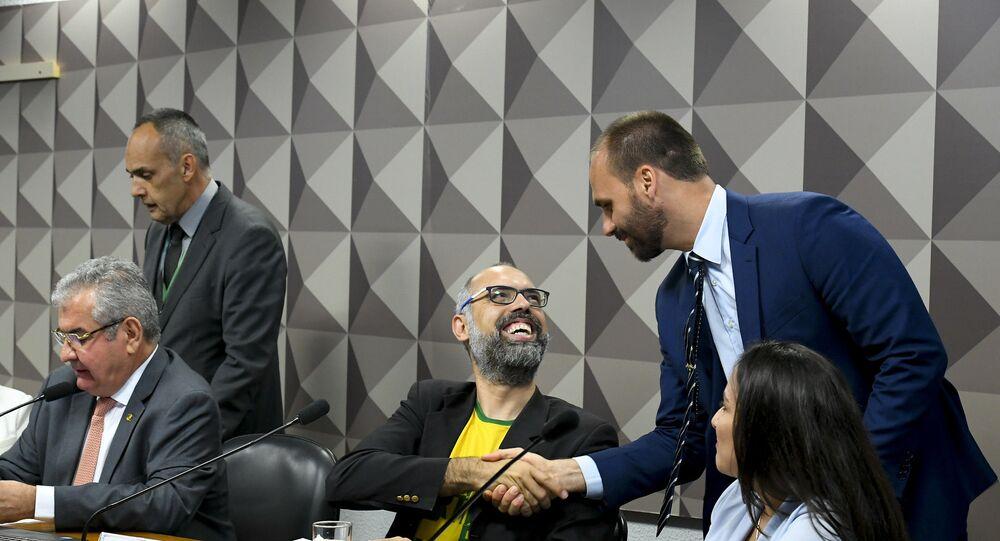 O blogueiro Allan dos Santos cumprimenta o deputado federal Eduardo Bolsonaro (PSL-SP) durante sessão da CPMI das Fake News, em 5 de novembro de 2019.