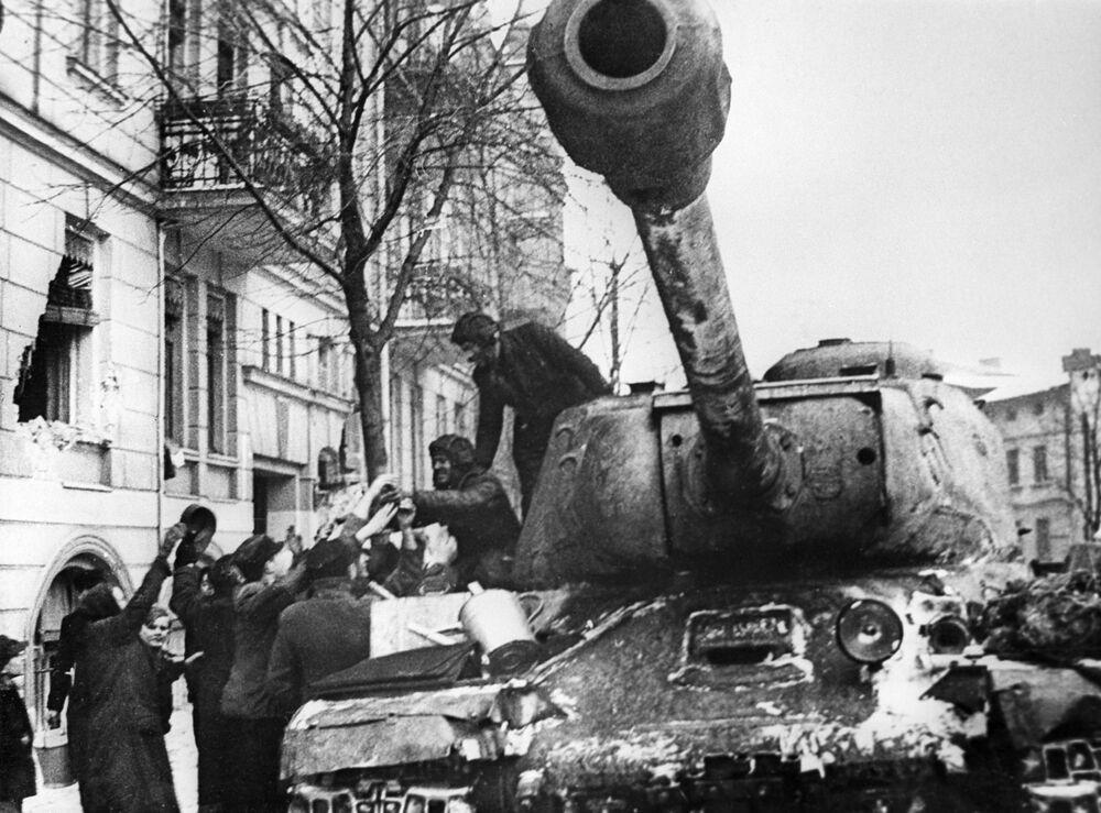 Moradores da cidade polonesa de Poznan saúdam soldados libertadores soviéticos em IS-2, tanque pesado nomeado em homenagem ao líder soviético Josef Stalin