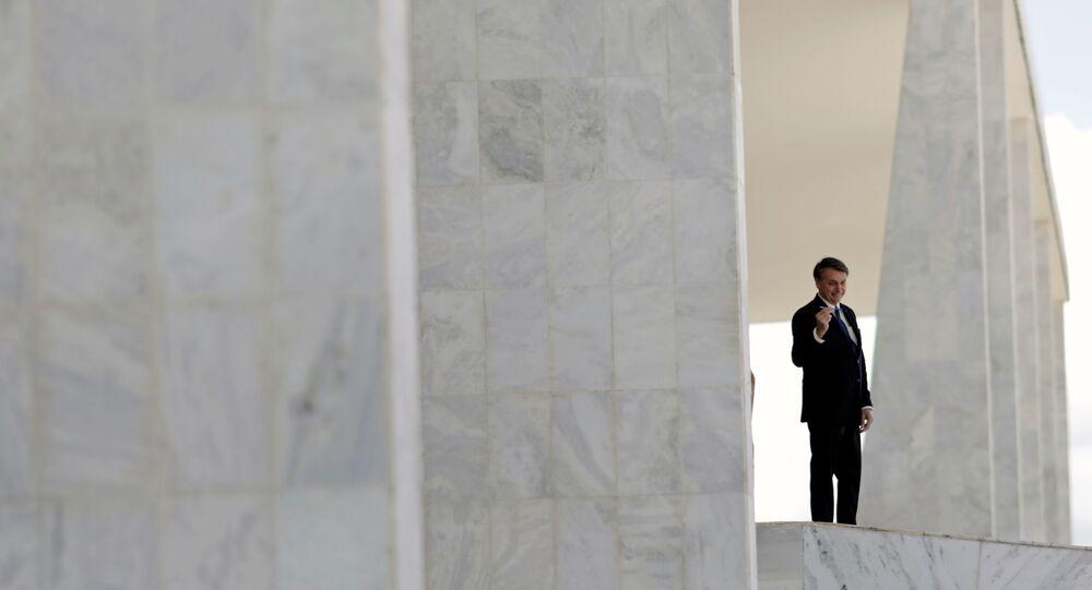 Presidente Jair Bolsonaro exibe caneta enquanto desce a rampa do Palácio do Planalto, em Brasília, 27 de abril de 2020