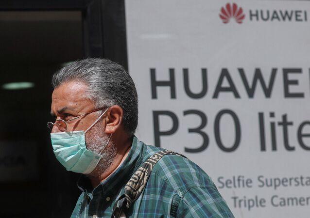 Homem com máscara protetora devido à COVID-19 passando por loja da Huawei no Cairo, Egito, 31 de março de 2020