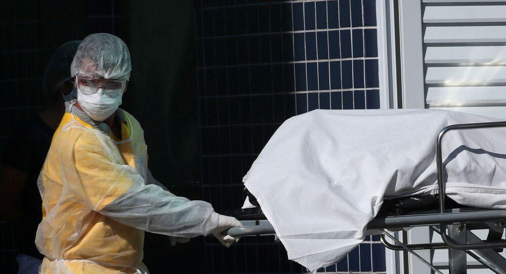 Funcionária de hospital retira o corpo de uma vítima da COVID-19 no Rio de Janeiro