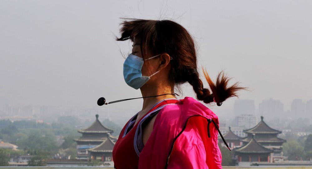 Mulher usando máscara e luvas faz exercícios no parque Jingshan, em Pequim, na China, 30 de abril de 2020