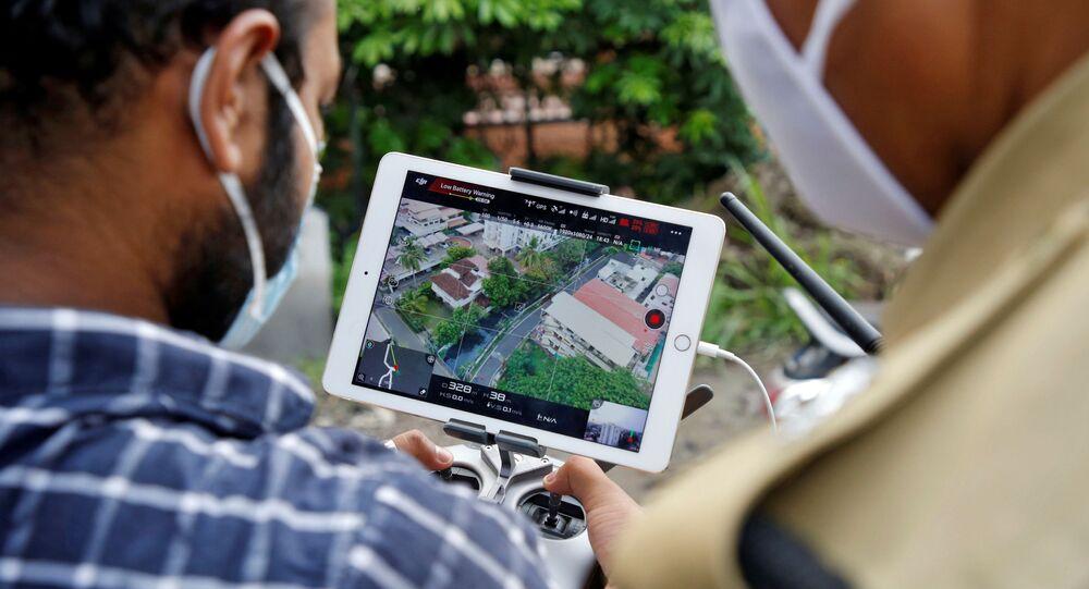 Policiais usam drone para monitorar o movimento de pessoas em uma área residencial depois que esta foi declarada local sensível pelas autoridades durante o isolamento nacional para retardar a propagação da doença do coronavírus (COVID-19) em Kochi, Índia, 24 de abril de 2020