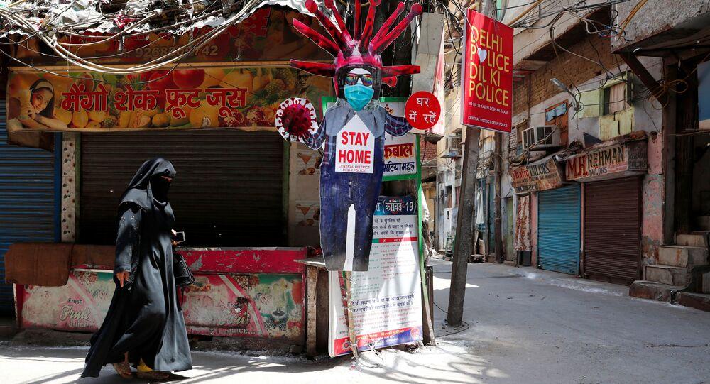 Mulher passa por uma figura em cartão representando o coronavírus e incentivando a ficar em casa em uma área residencial durante o isolamento para retardar a propagação da doença do coronavírus (COVID-19) nos bairros antigos de Deli, Índia, 30 de abril de 2020
