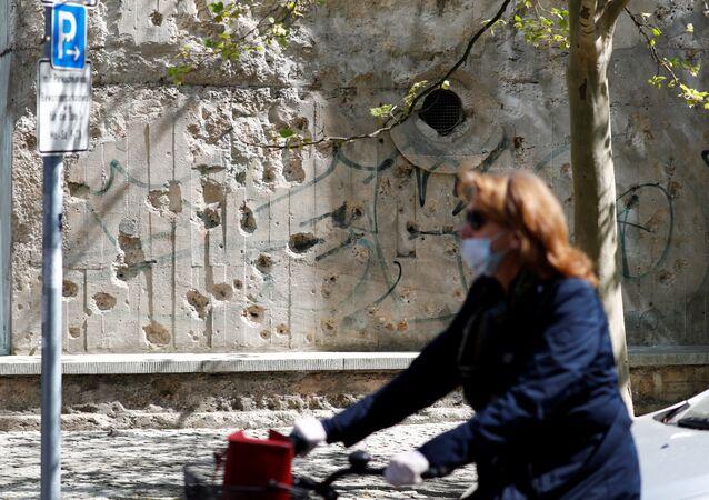 Mulher com máscara para se proteger do coronavírus passa com bicicleta por rua de Berlim, na Alemanha