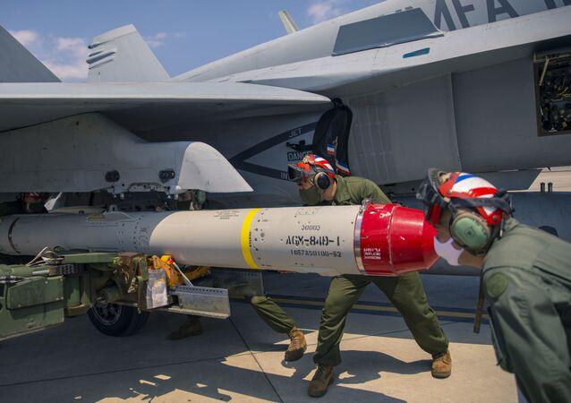 Militares norte-americanos carregam mísseis AGM-84D Harpoon ao F/A-18 Hornet na Estação Aérea de Iwakuni, no Japão