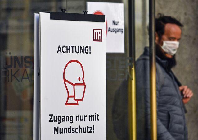 Aviso sobre o novo coronavírus na frente de loja de conveniência na cidade de Muenster Cuidado! Entre somente utilizando máscara, na Alemanha, 30 de abril de 2020
