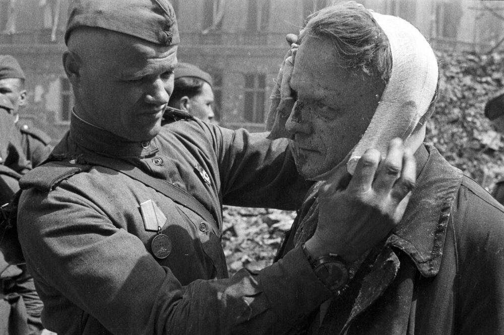 Soldado soviético faz curativo em morador de Berlim ferido