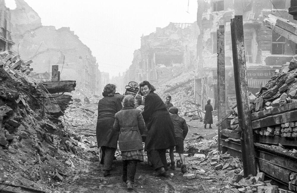 Moradores de Berlim voltam para suas casas por ruas com escombros após o fim dos combates