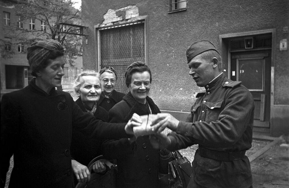 Soldado soviético distribui pães a mulheres de Berlim, em 7 de maio de 1945