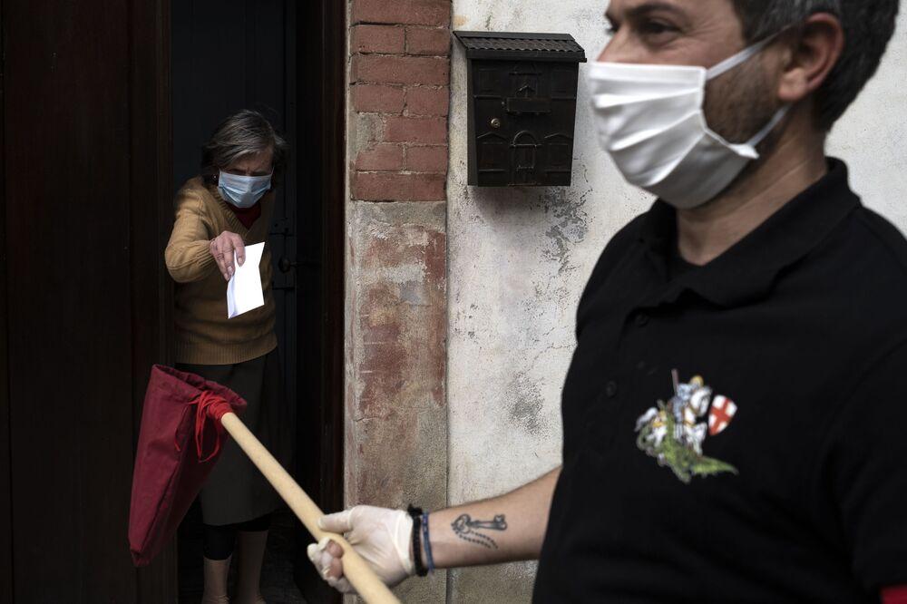 Mulher entrega dinheiro a membro da fazenda San Giorgio na Itália
