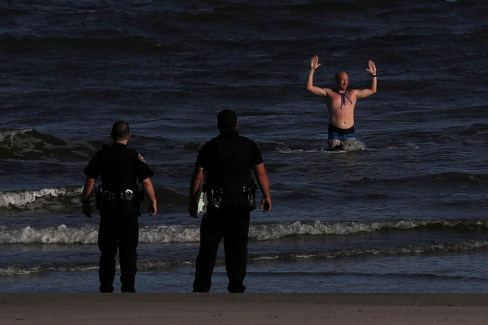 Homem sai do mar após ser detido pela polícia do Texas