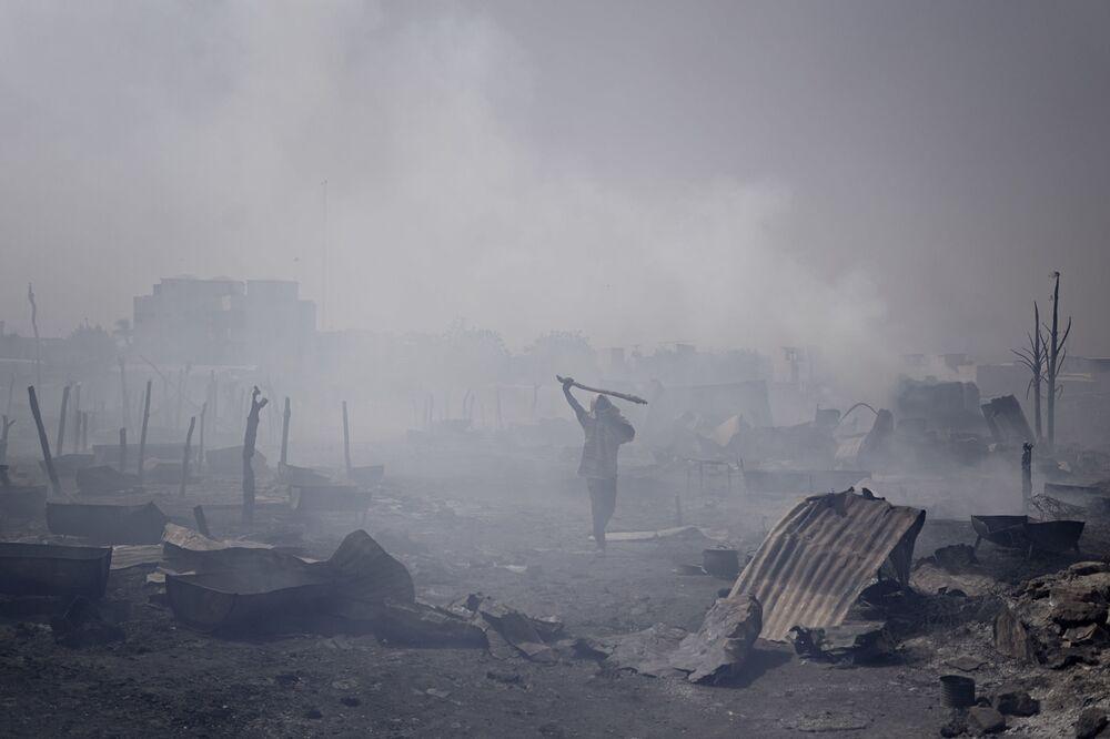 Homem caminha entre tendas queimadas em um campo de deslocados em Mali