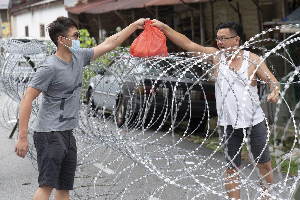 Homem passando sacola através de arame farpado na Malásia