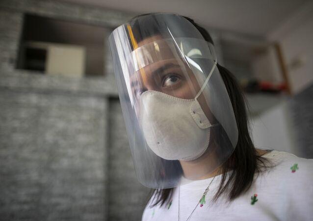 Uma mulher usando máscara e escudo facial (foto de arquivo)