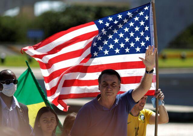 O presidente brasileiro, Jair Bolsonaro, acena em frente a uma bandeira dos Estados Unidos durante protesto pró-intervenção militar em Brasília, em 3 de maio de 2020.