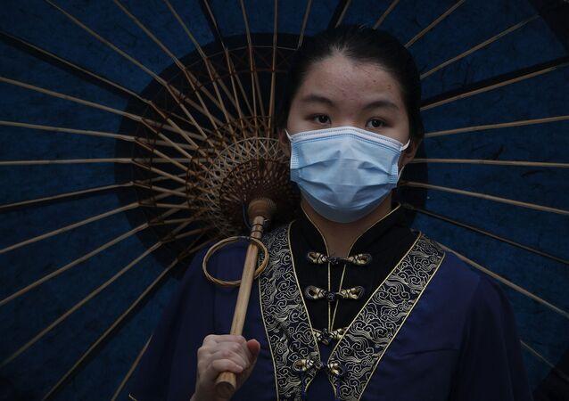 Chinesa usando vestes tradicionais e máscara protetora, em Pequim, 3 de maio de 2020
