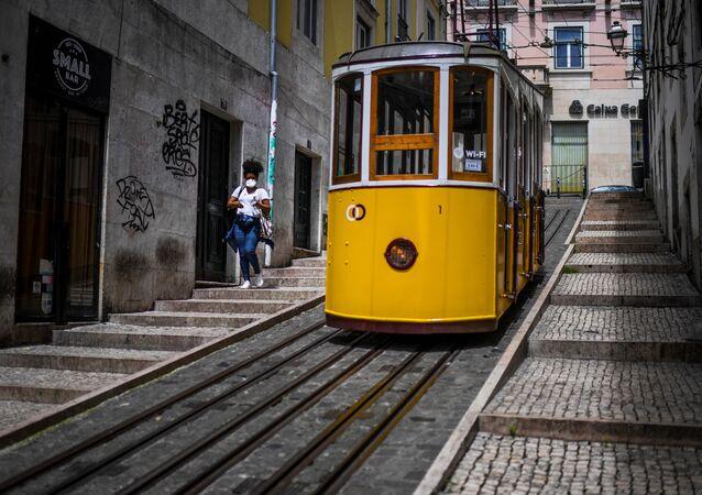 Mulher de máscara caminha em Lisboa, no primeiro dia de desconfinamento em Portugal