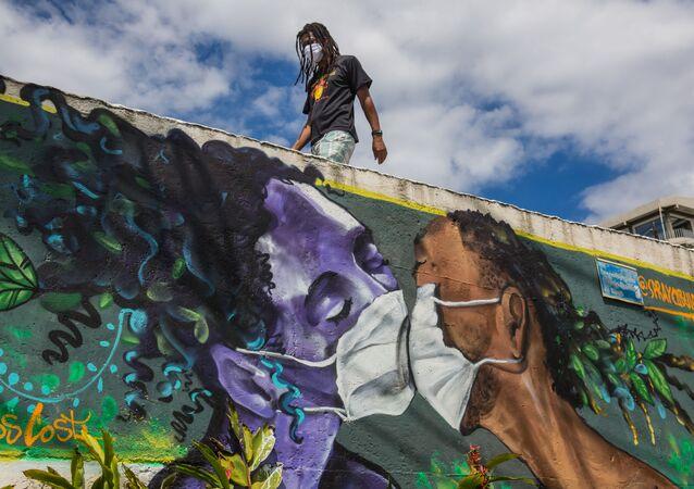 Homem usa máscara protetora próximo a muro grafitado por Marcos Costa, em Salvador