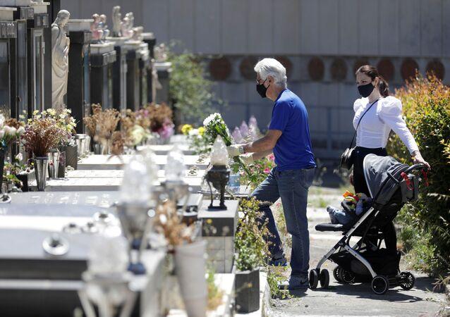 Homem usando máscara facial protetora coloca flores em um túmulo no cemitério de Catânia, que reabriu hoje, quando a Itália inicia um desconfinamento gradual em meio à propagação da doença do coronavírus (COVID-19), Itália, 5 de maio de 2020