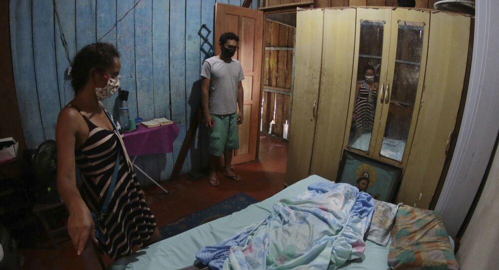 Parentes ficam ao lado do corpo de uma vítima de 86 anos da COVID-19 em Manaus (AM)