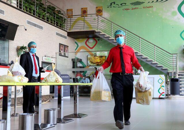 Funcionário de restaurante em Riad, capital da Arábia Saudita, prepara pedido para entrega (arquivo)