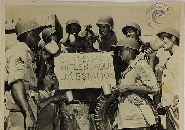Homens da Força Expedicionária Brasileira (FEB) seguram placa com provocação a Adolph Hitler.