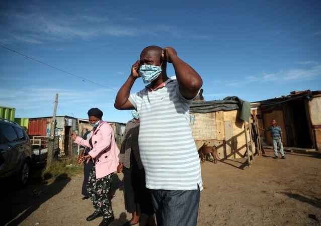 Voluntários colocam máscaras enquanto se preparam para distribuir alimentos em 17 de abril de 2020, durante o período de confinamento em combate à COVID-19 na Cidade do Cabo, África do Sul.