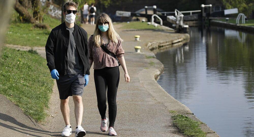Casal anda com máscaras como prevenção da COVID-19 no Reino Unido (foto de arquivo)