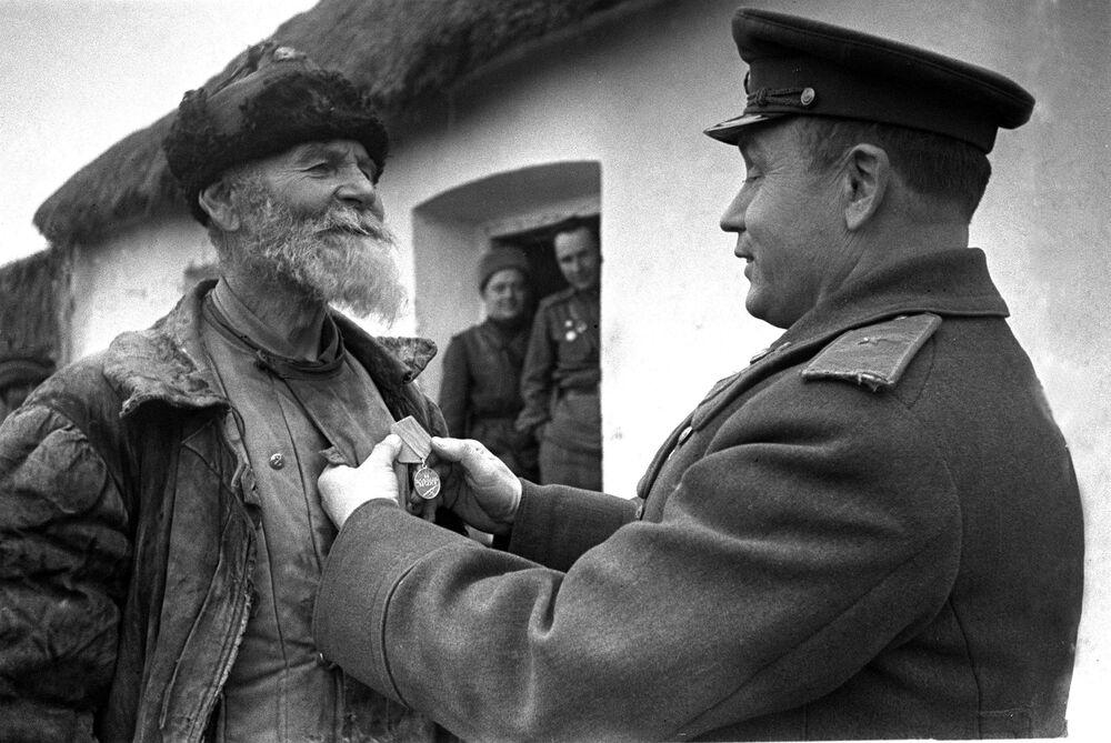 Comandante de divisão condecora o agricultor Pomkin no terceiro fronte ucraniano, em 1945