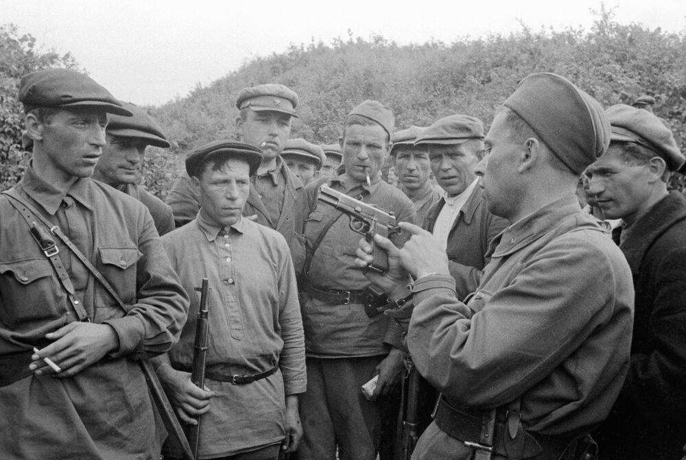 Comandante de destacamento partisan mostra armamentos a combatentes na região russa de Smolensk