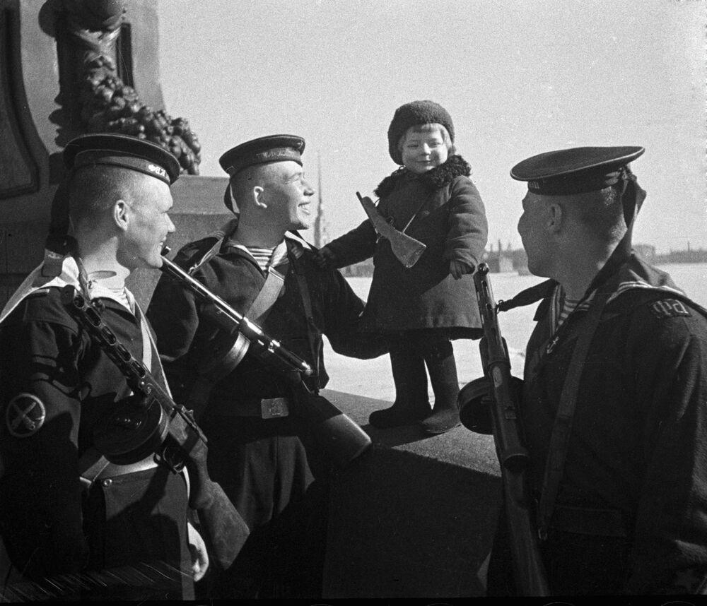 Marinheiros da Frota do Báltico da União Soviética conversam com garotinha órfã durante a evacuação de crianças de Leningrado, que estava sitiada
