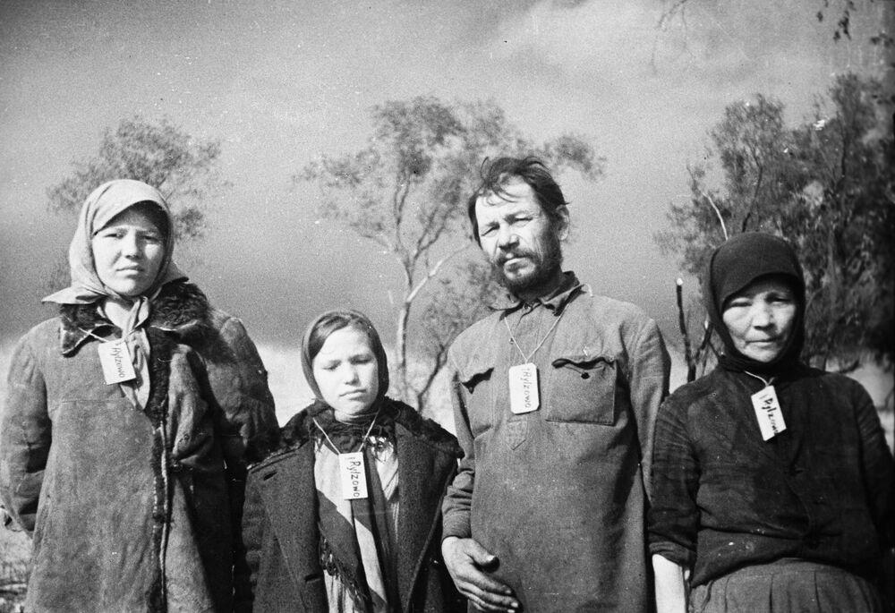Moradores do vilarejo de Zubtsovo, ocupado pelos alemães, com placas com o nome de seu vilarejo