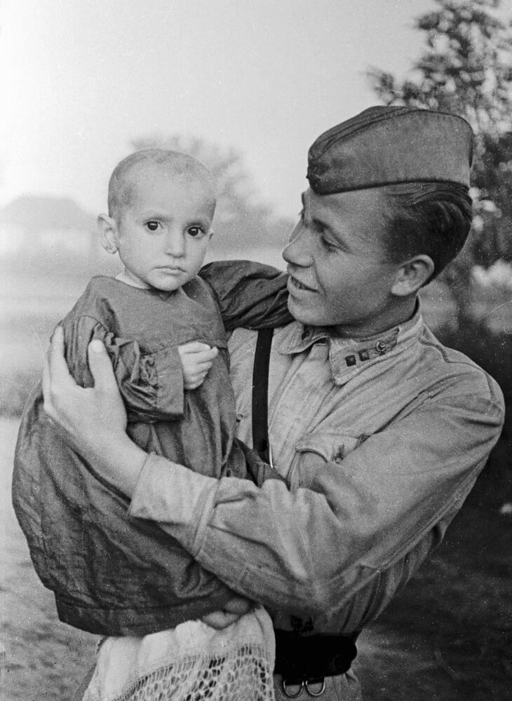 Oficial soviético segura no colo menina salva por ele do vilarejo de Elkhotovo