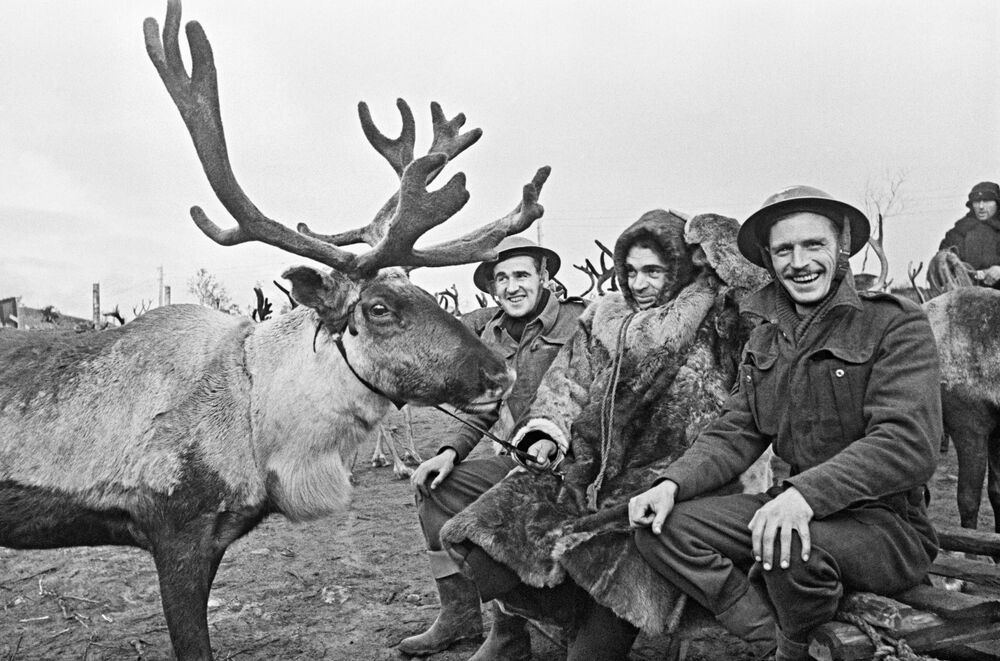 Criador de renas soviético com mecânicos britânicos em aeródromo no Ártico, 1942