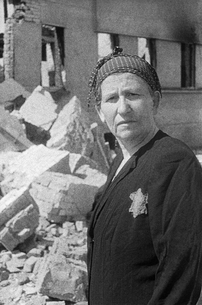 Moradora de gueto judeu entre escombros de sua casa