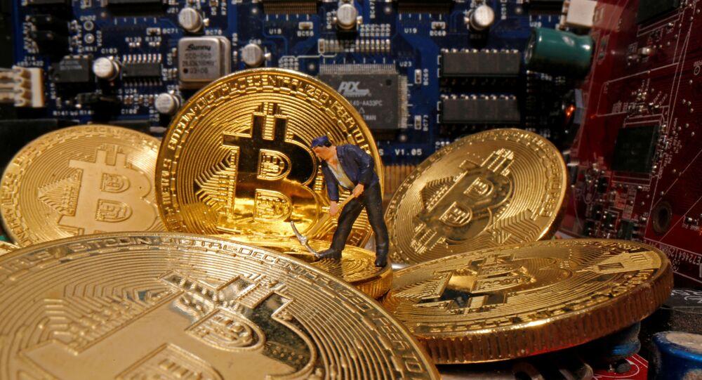 Pequena figura de brinquedo e representações da moeda virtual bitcoin em uma placa mãe, 17 de abril de 2020