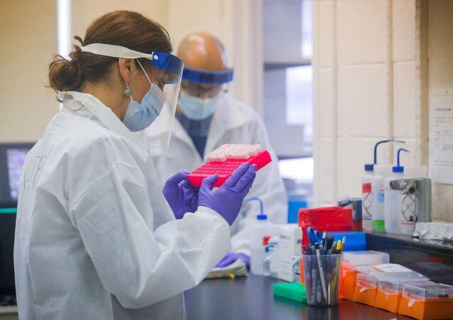 Cientistas trabalham em um laboratório testando amostras da COVID-19 no departamento de saúde de Nova York, durante o surto da doença do coronavírus (COVID-19) na cidade de Nova York, EUA, 23 de abril de 2020