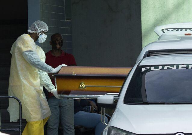 Profissional de saúde coloca um caixão de um paciente vítima da COVID-19 no Rio de Janeiro