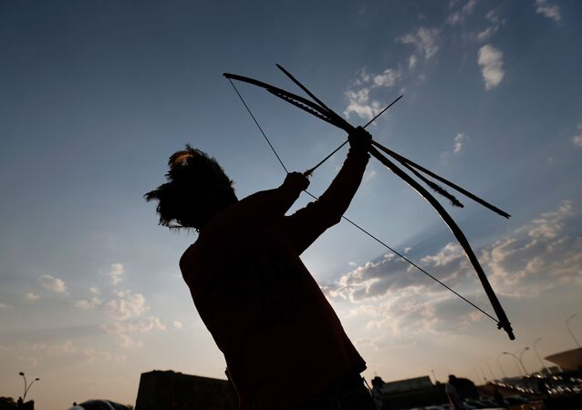 Índio da tribo Guarani Kaiowa com tradicional arco e flecha, em Brasília, Brasil (imagem de arquivo)