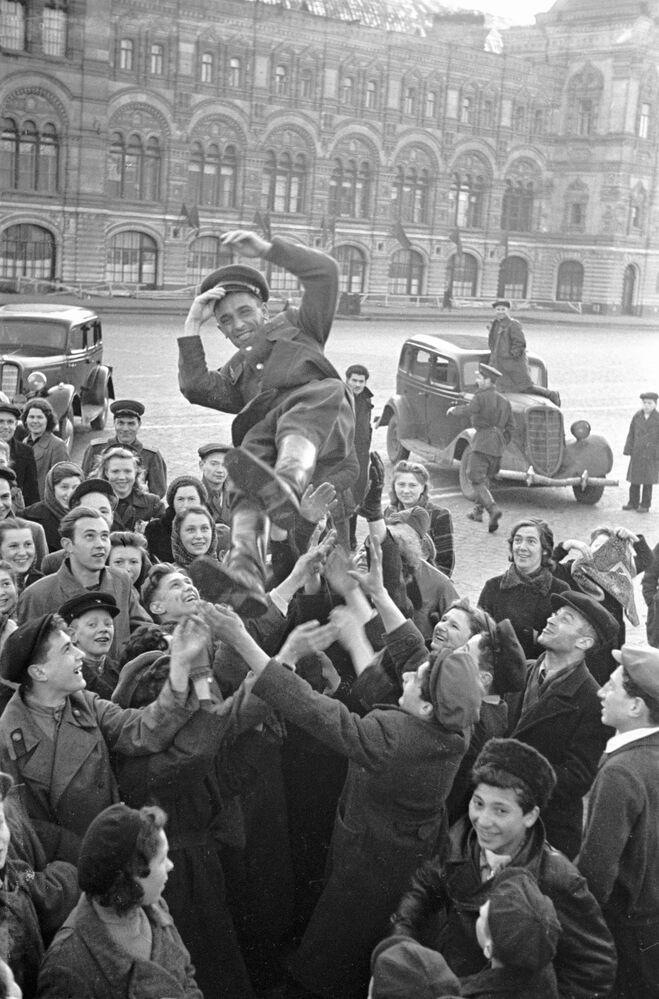 Grupo de pessoas celebra vitória da União Soviética frente à Alemanha nazista