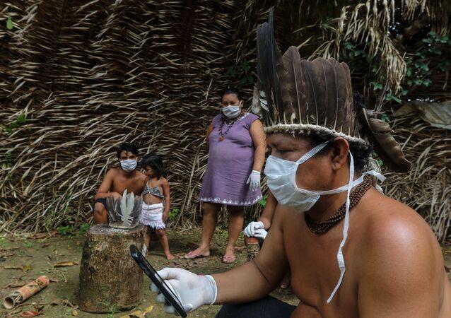 Membros da tribo indígena Saterê Mawé usando máscaras durante atendimento médico via celular com médico em São Paulo na comunidade Sahu-Apé, no município amazonense de Iranduba