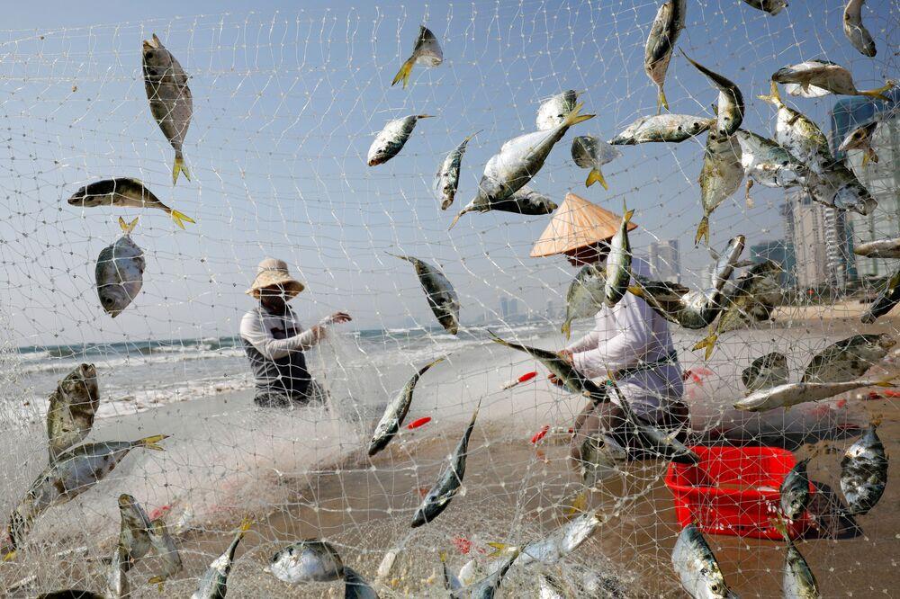 Pescadores pegam peixe em praia na cidade vietnamita de Da Nang durante a pandemia de COVID-19